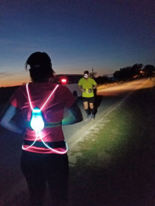 runner wearing a blinking vest and headlamp waiting for another runner