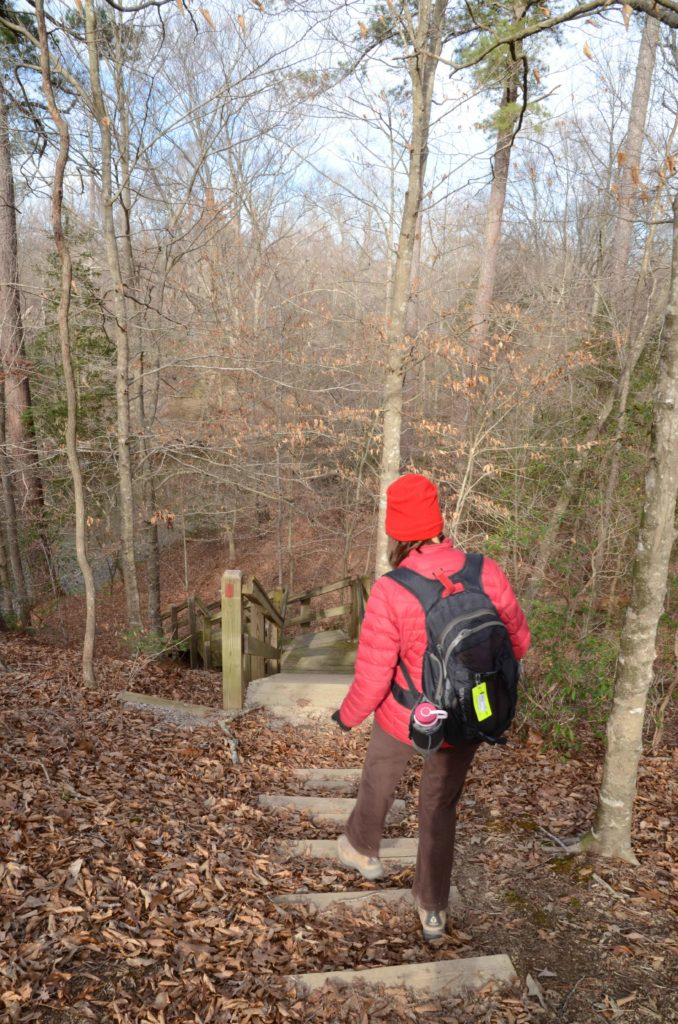 Woman walking down stairs of steep trail at Medoc Mountain State Park