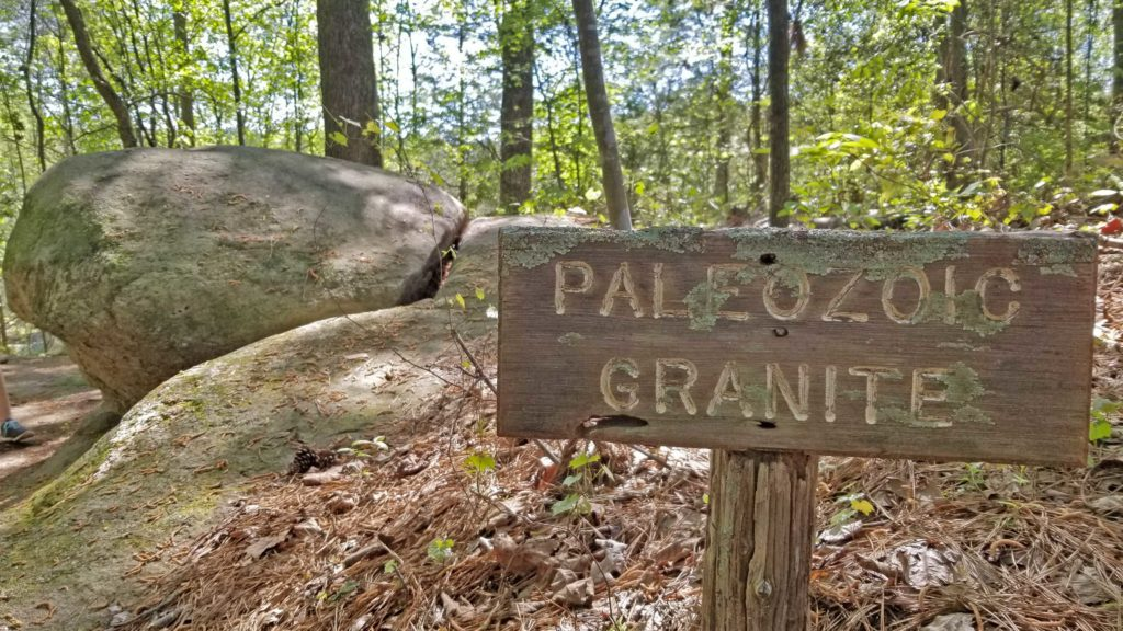 """Rock outcrop at DeHart Botanical Gardens with a sign that says """"paleozoic granite"""""""