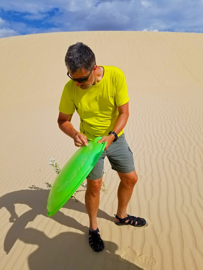 Man waxing green sled standing on a sand dune