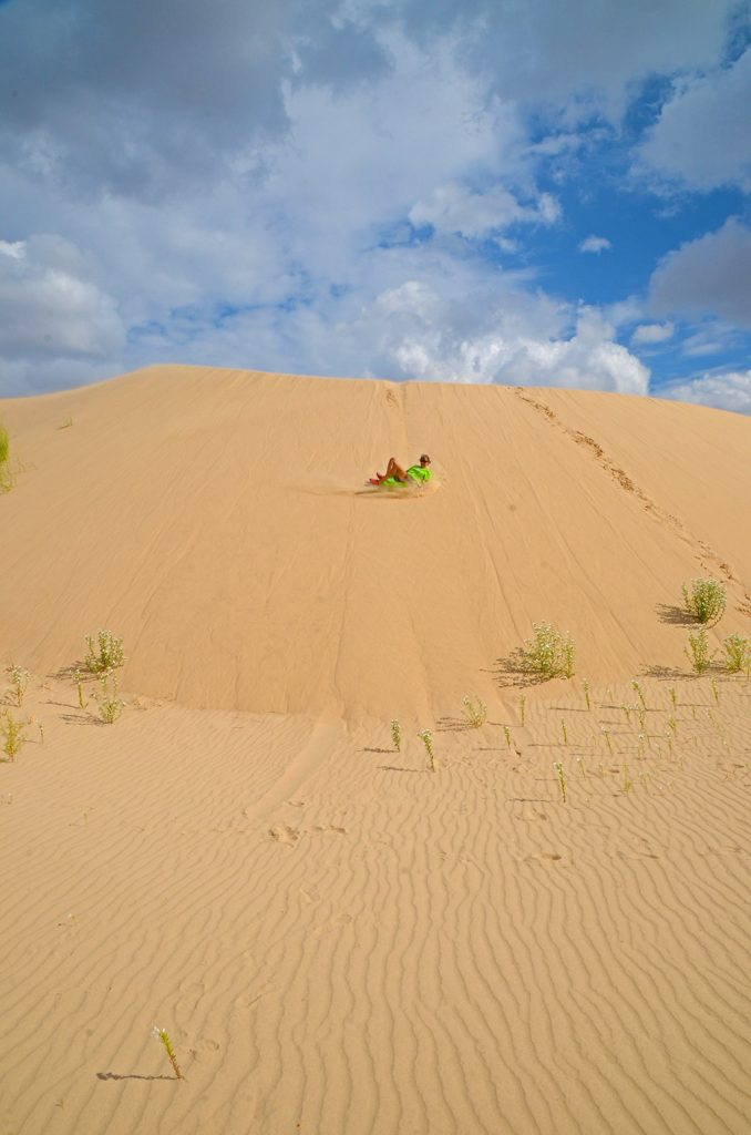 Woman sliding down a sand dune on a disk
