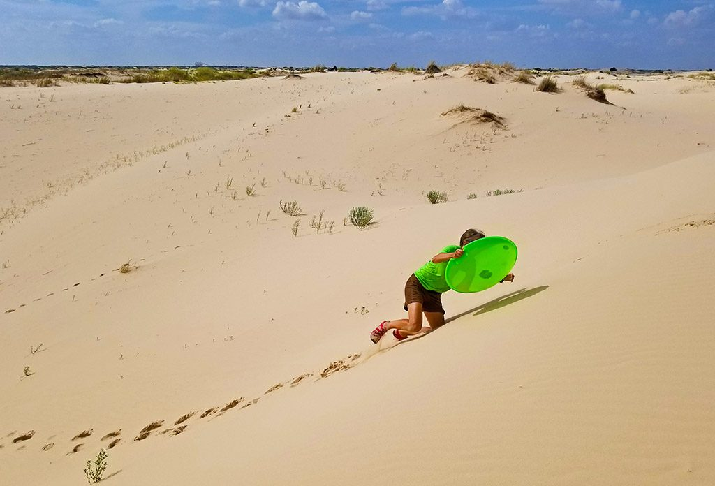 Woman struggling to climb a sand dune with a sled
