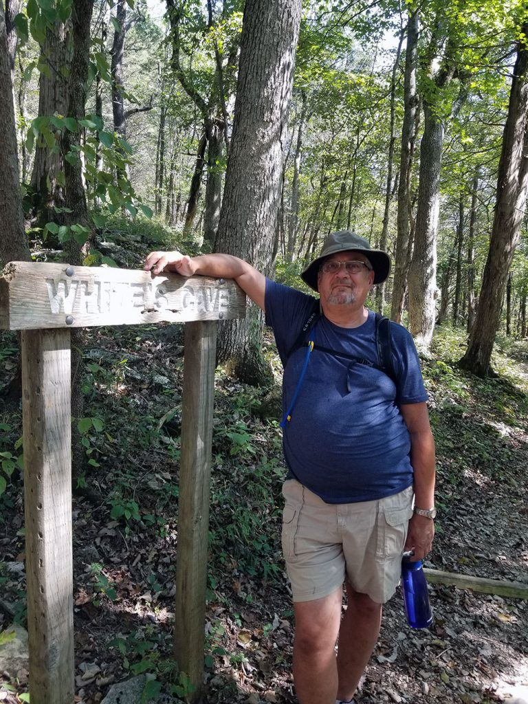 Man standing beside White's Cave Sign