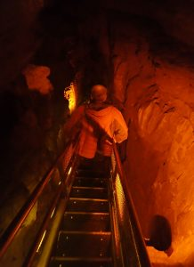 Man descending narrow stairs in cave