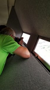Man taking picture out narrow river at top of St Louis Arch