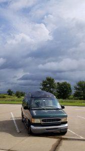 storm clouds behind green van