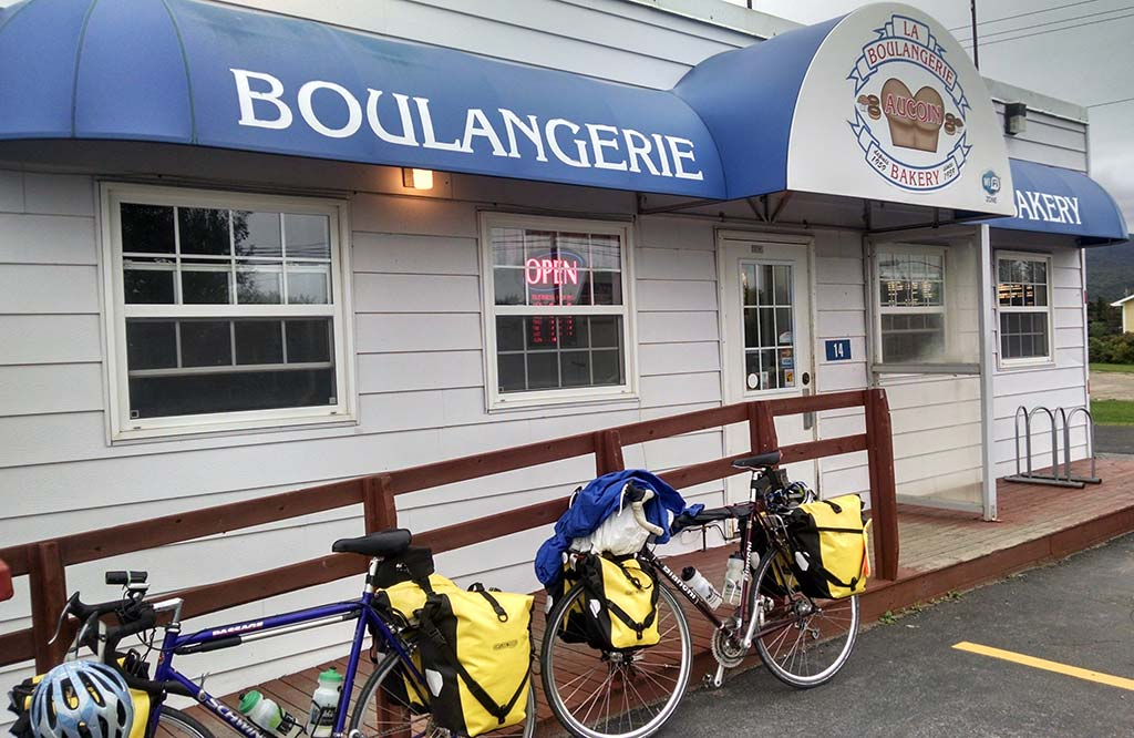 Touring bikes loaded with panniers outside Boulangerie Bakery in Cape Breton