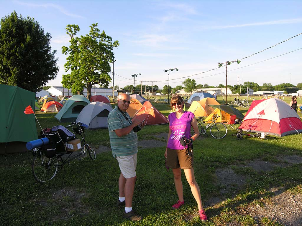 Two people standing in front of many tents