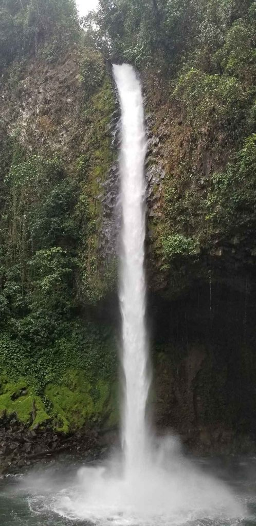 La Fortuna Waterfall - tall, skinny fall into a pool of water surrounded by jungle