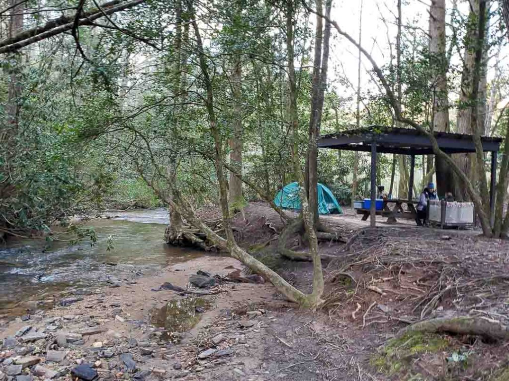 Green tent beside sheltered picnic table along Long Creek